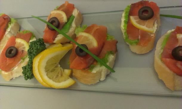 Тартинки с сёмгой слабосолёной подаются с маслинами, лимоном и зеленью