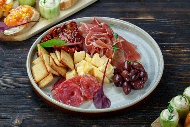 Ассорти закусок - оливки, сыр чеддер, вяленые томаты, два вида итальянских колбасок, крекеры